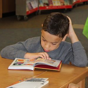 A second-grader sat down immediately to start reading his new book.