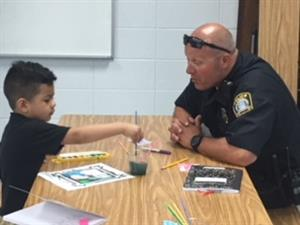 An LFUCG officer works with a student creating art during reading camp.