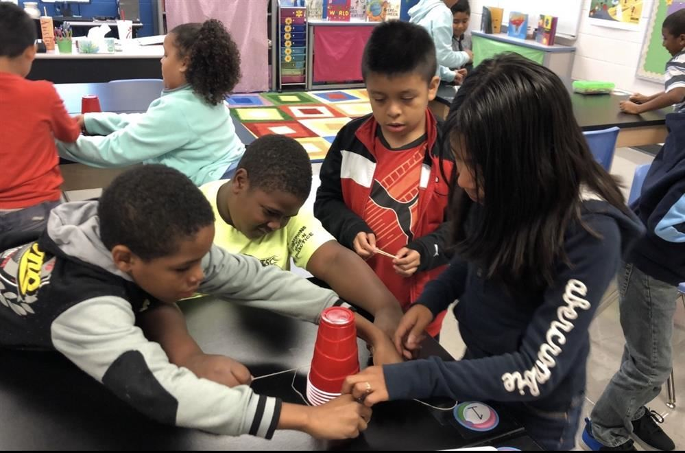 In STEAMS class, youngsters use string and plastic cups in a problem-solving group activity.