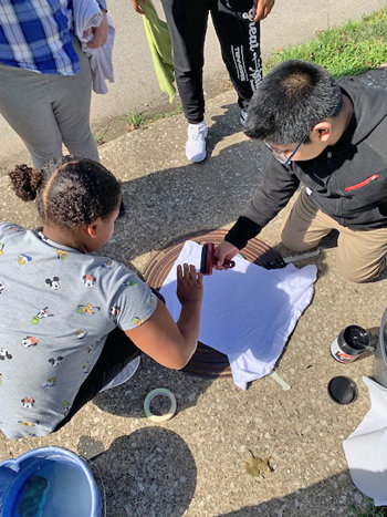 Students press a T-shirt onto a manhole cover to copy the design.