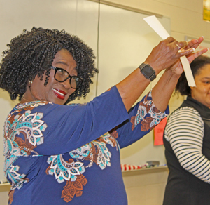 A volunteer pretends to snap a selfie in a self-esteem exercise for teenagers.