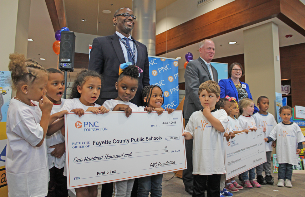 Children from Lexington's One Parent Scholar House with the ceremonial checks from the PNC Foundation