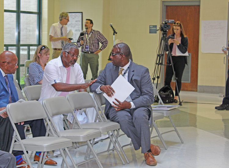 Superintendent Manny Caulk (right) chatted with community leaders before the news conference at Dunbar.