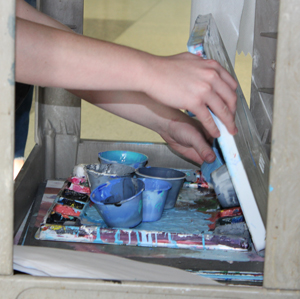 Students store their art supplies on a small cart.