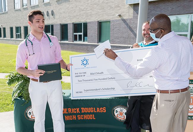 Bilal Chhadh receives the check from Superintendent Manny Caulk (right).