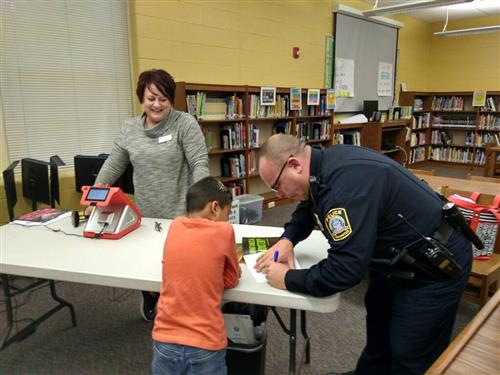 Officer Brandon helping students pick out books