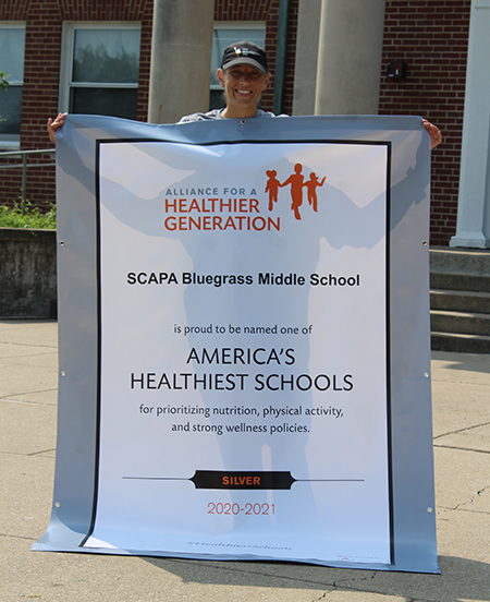 P.E. and health teacher Angela Stark with SCAPA's latest banner