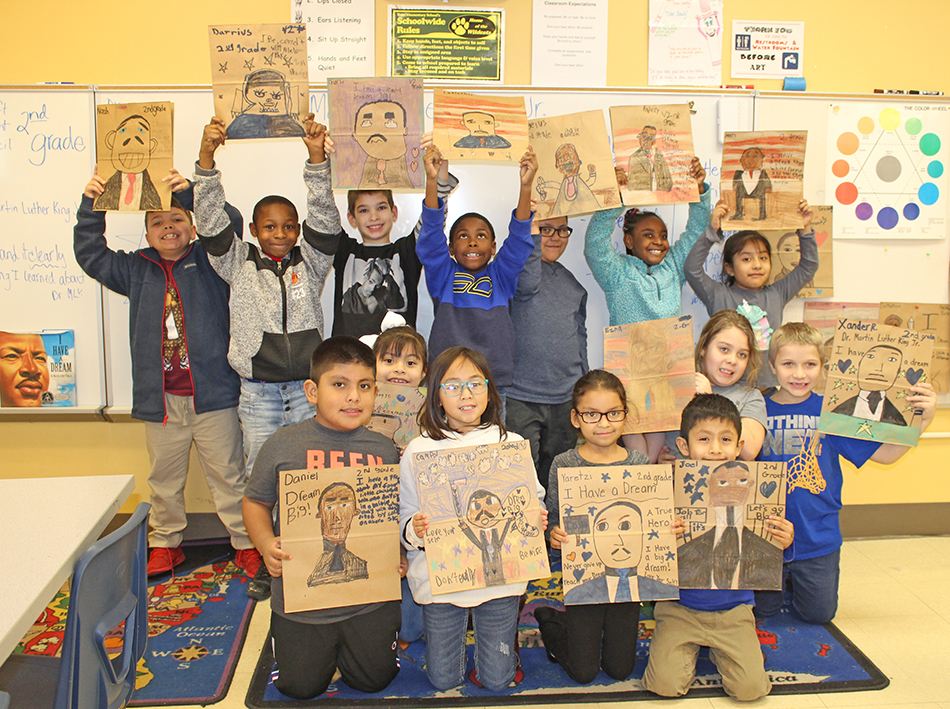 Second graders are proud of their finished grocery bags.