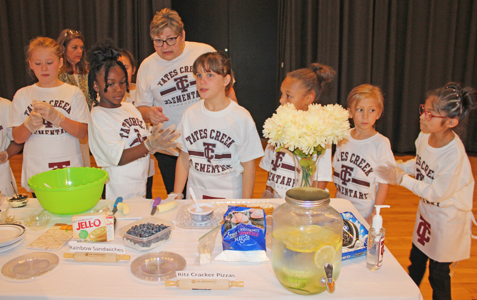 Karen Miller and members of the fall 2019 cooking club presented samples at a school board meeting.