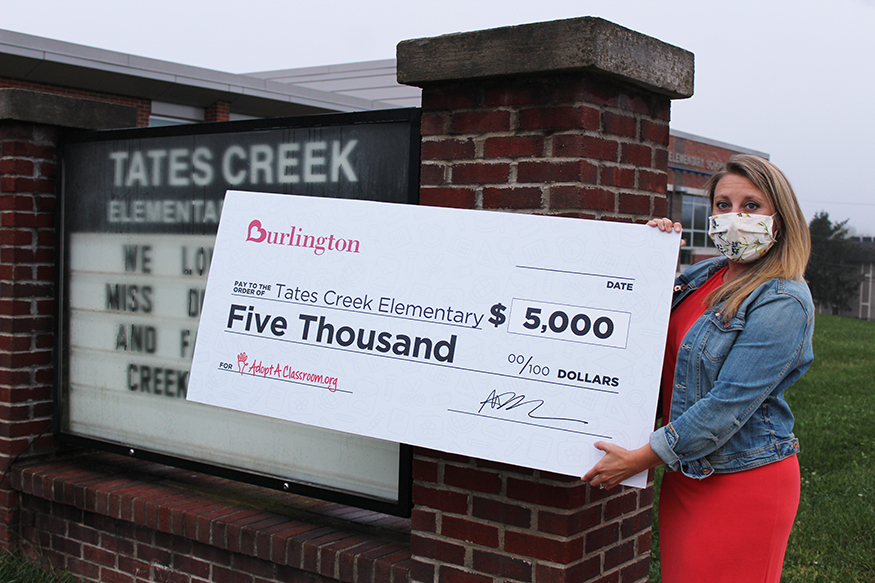 Administrative Dean Holly McCauley displays the big check outside the school.