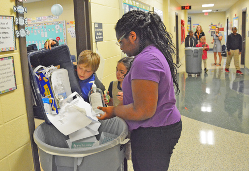 Students look for contaminants as they empty recycling bins.