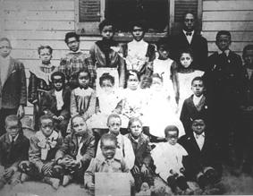 An old black and white picture of a group of african americans dressed in school uniform.