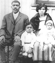 Old picture of black family. Father, mother, a toddler son and an infant daughter.
