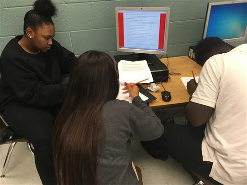 Three students work together at a computer to complete research.