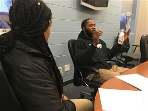 Nyema Morais sits at a conference table and shares his story with students.
