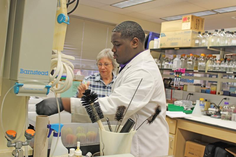 Dorian Cleveland, a senior at Carter G. Woodson Academy, works alongside lab manager Etta Nuckles.